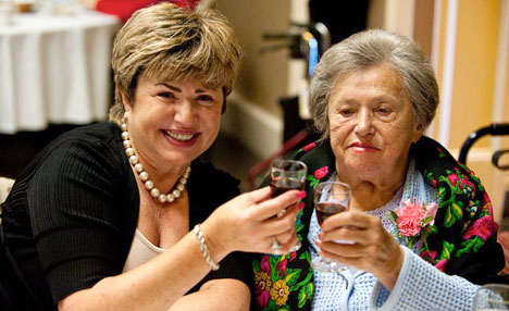 Resident and family member at a birthday luncheon, making a toast