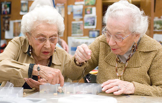 Two residents stringing beads in the creative arts studio