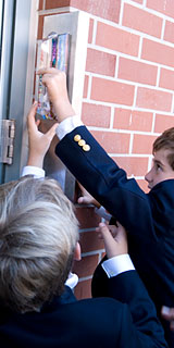 Two boys hanging a mezuzah
