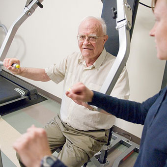 Resident using chest press machine in the fitness center