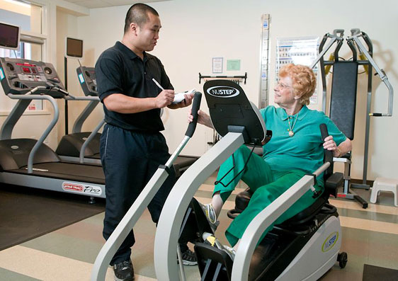 Staff training a resident on the fitness center's Nustep machine