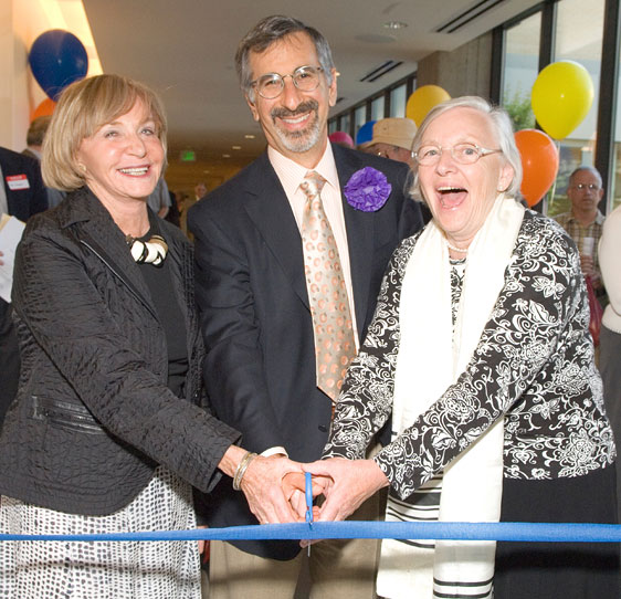 Three community leaders cutting the ribbon at the opening celebration