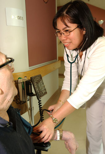 Nurse Assistant checks blood pressure of resident